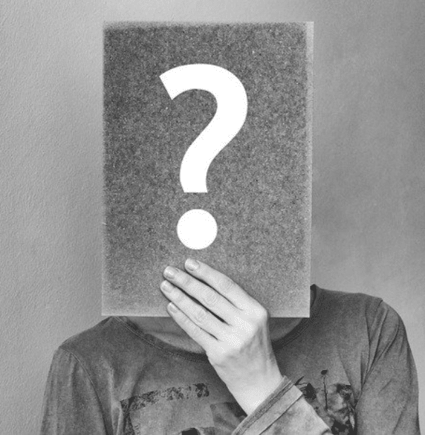 person holding question mark in front of face