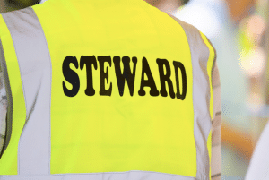 person wearing yellow safety vest that says steward